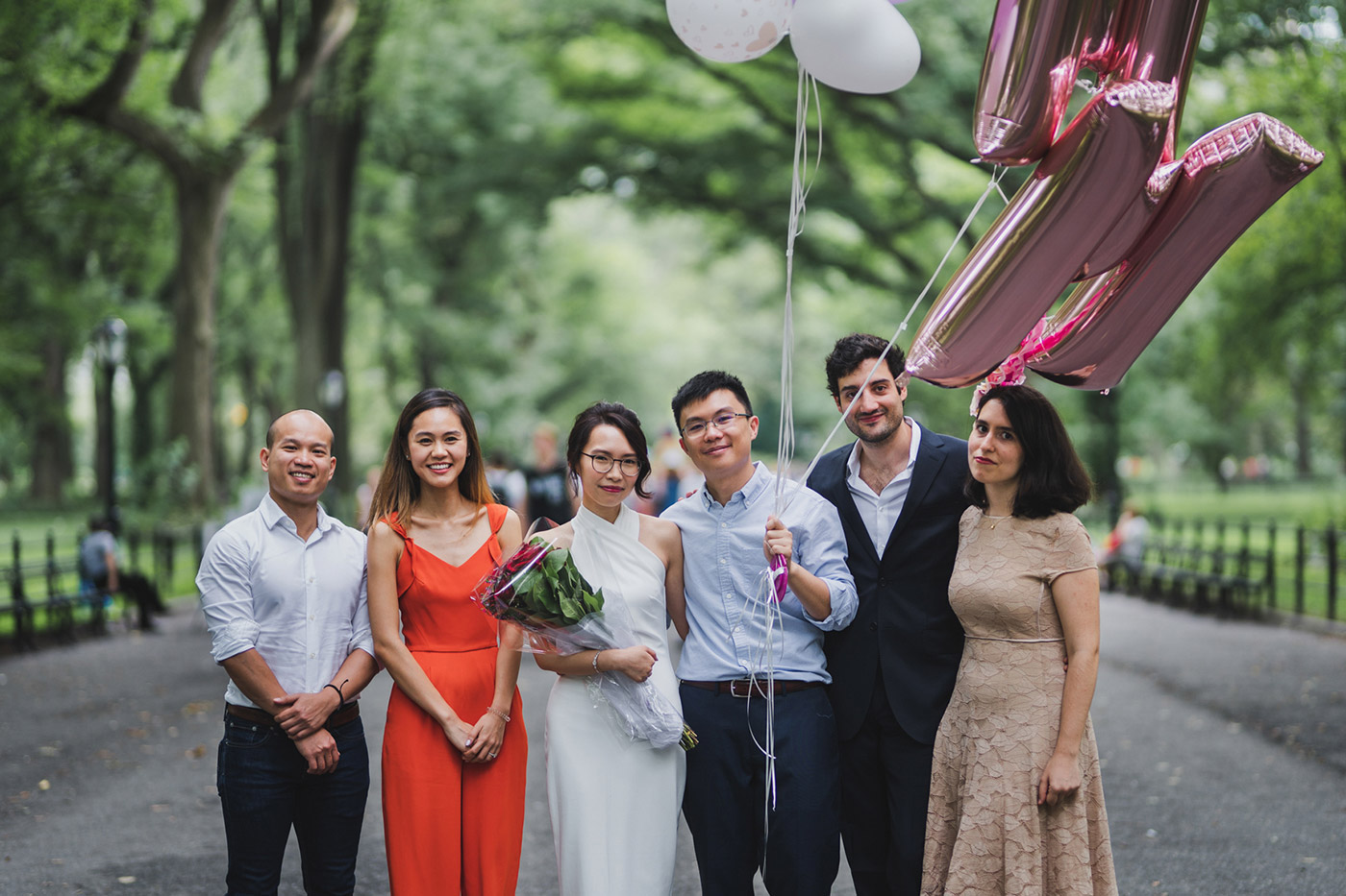 bride and groom with friends at a Central Park proposal