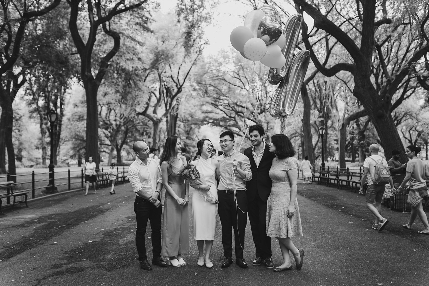 bride and groom with friends at a Central Park proposal (b&w)