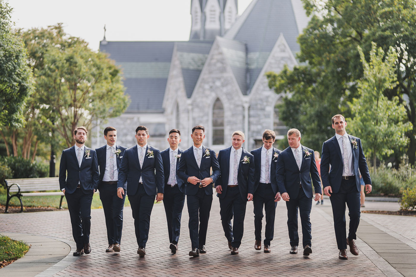 groom and groomsmen walking from a wedding at Saint Thomas of Villanova by Weddings by Hanel