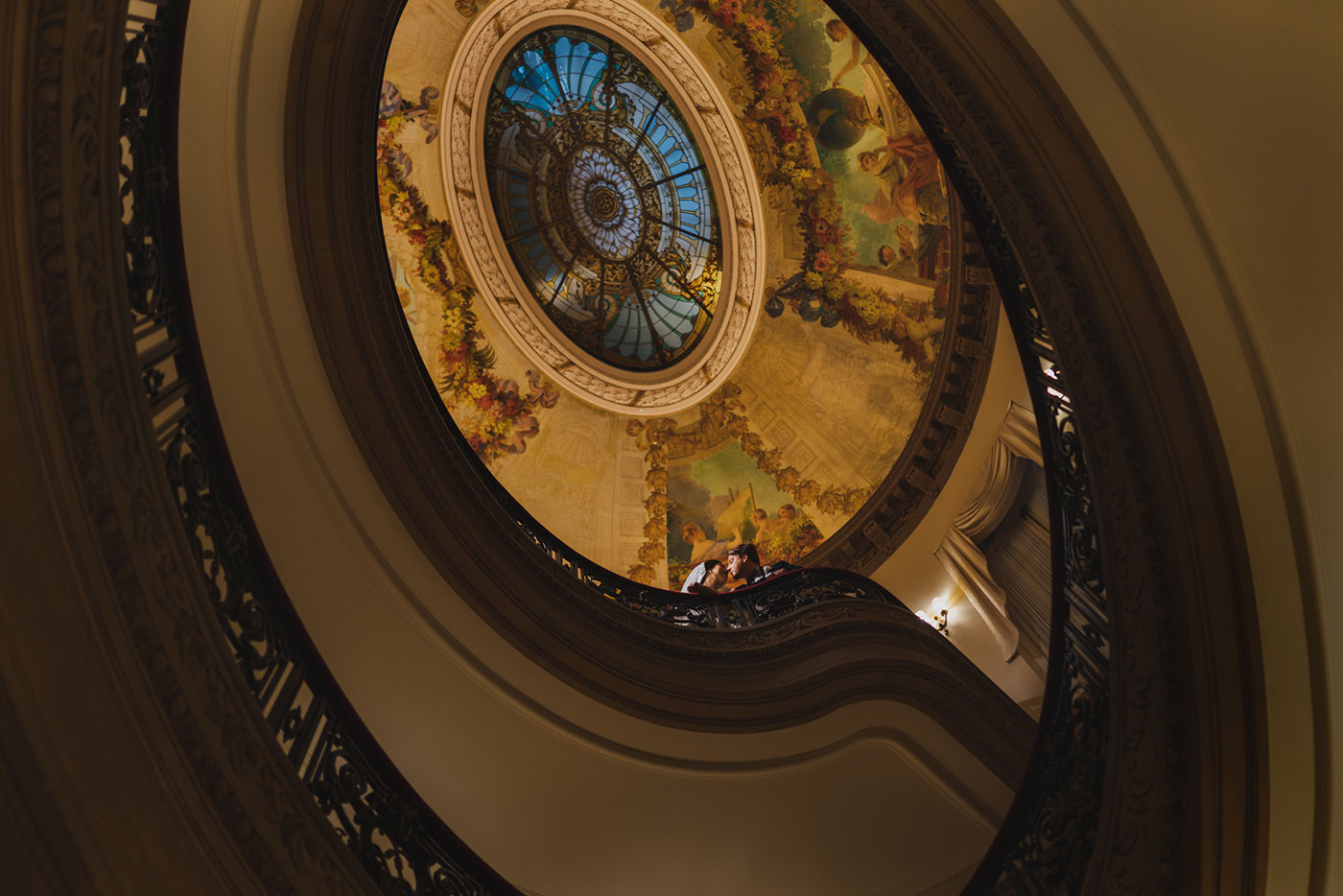 ceiling and spiral staircase portrait of bride and groom at the James Burden Kahn Mansion by Weddings by Hanel