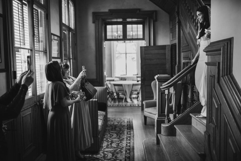 photojournalism shot of bride walking down stairs and mother taking photos