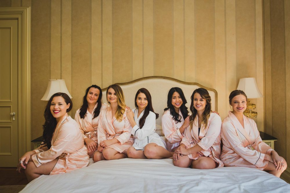 posing bride and bridesmaids in robes on an antique bed