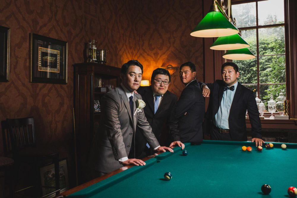 posing groom and groomsmen in the billiards room